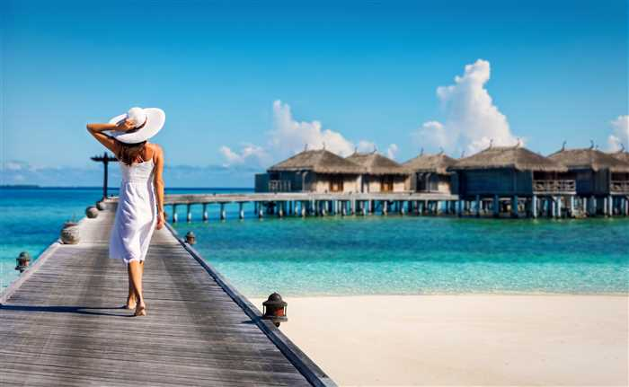 Hotel guest walking over a wooden jetty in the Maldives hotel